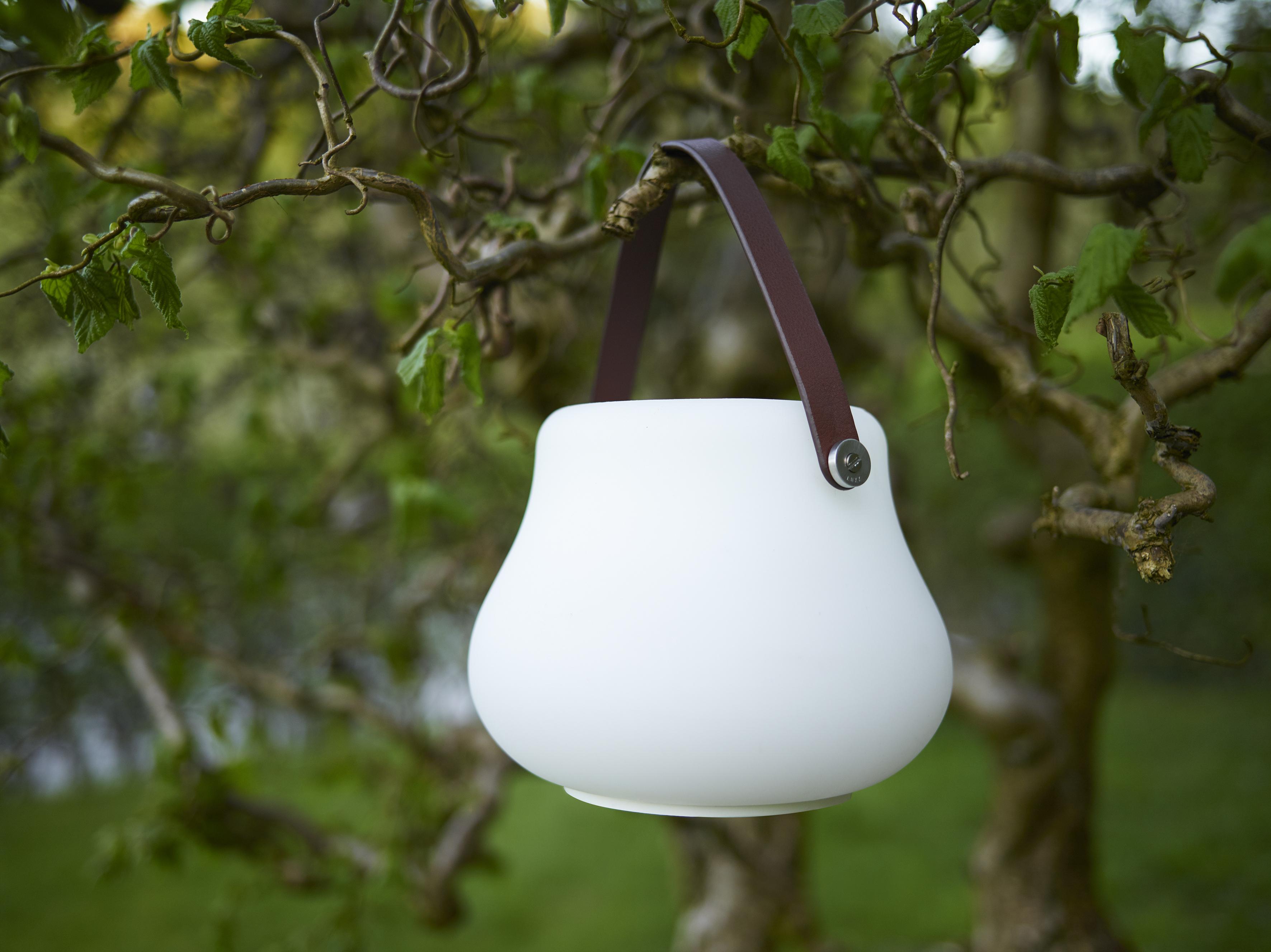 Ein kleiner leuchtender Blumentopf hängt an einem Baum