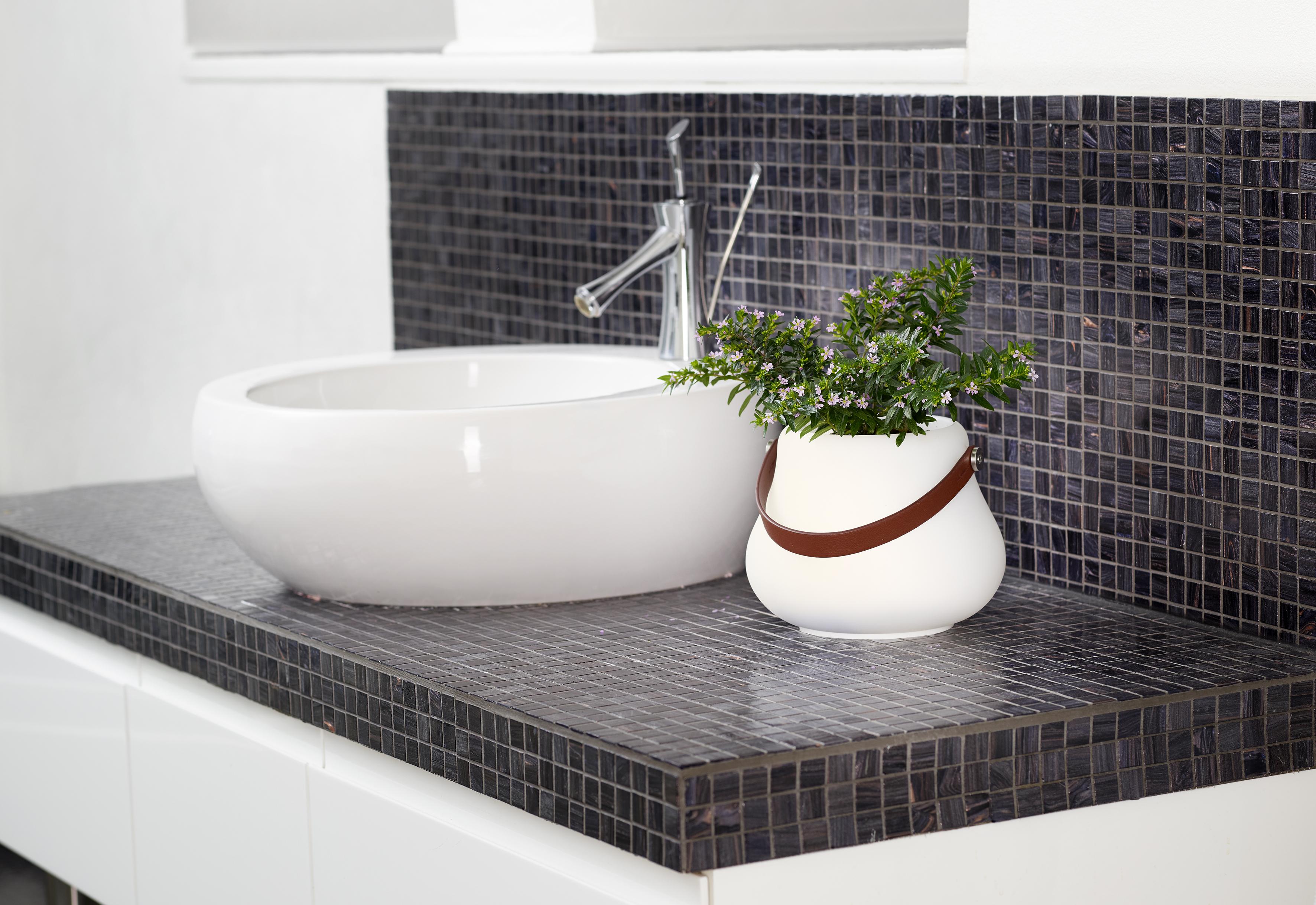 Ein kleiner leuchtender Blumentopf steht neben einem Waschbecken im Bad