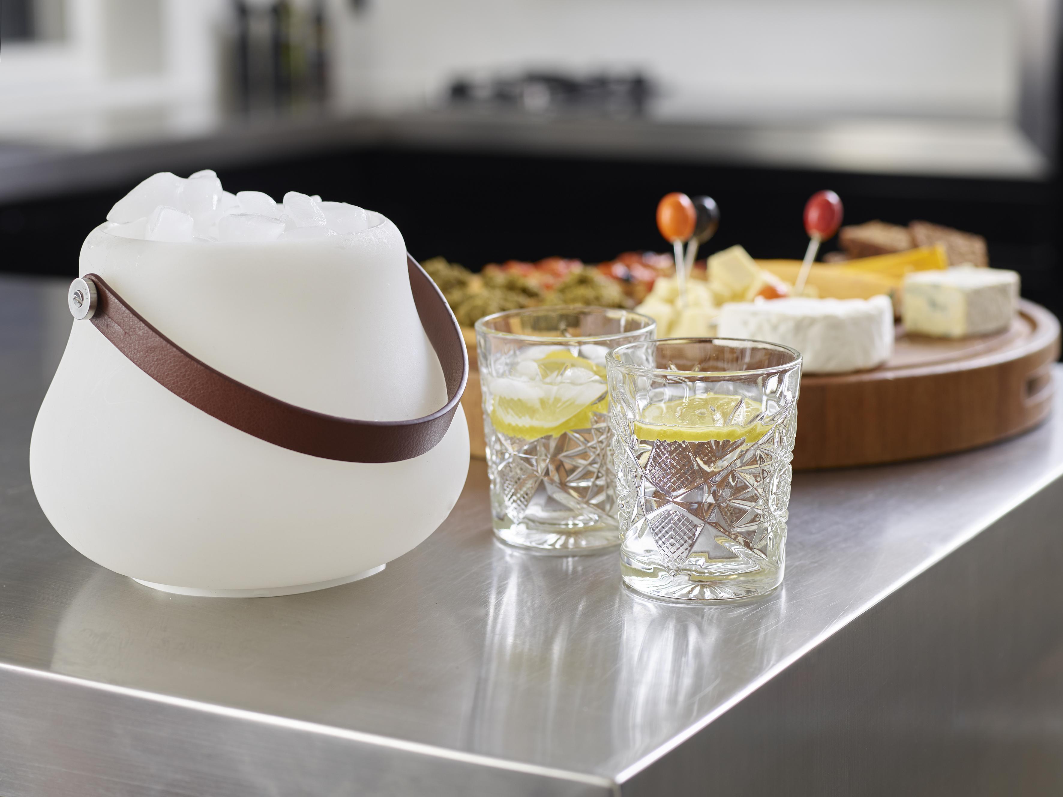 Ein kleiner leuchtender Blumentopf gefüllt mit Eiswürfeln auf der Küchentheke