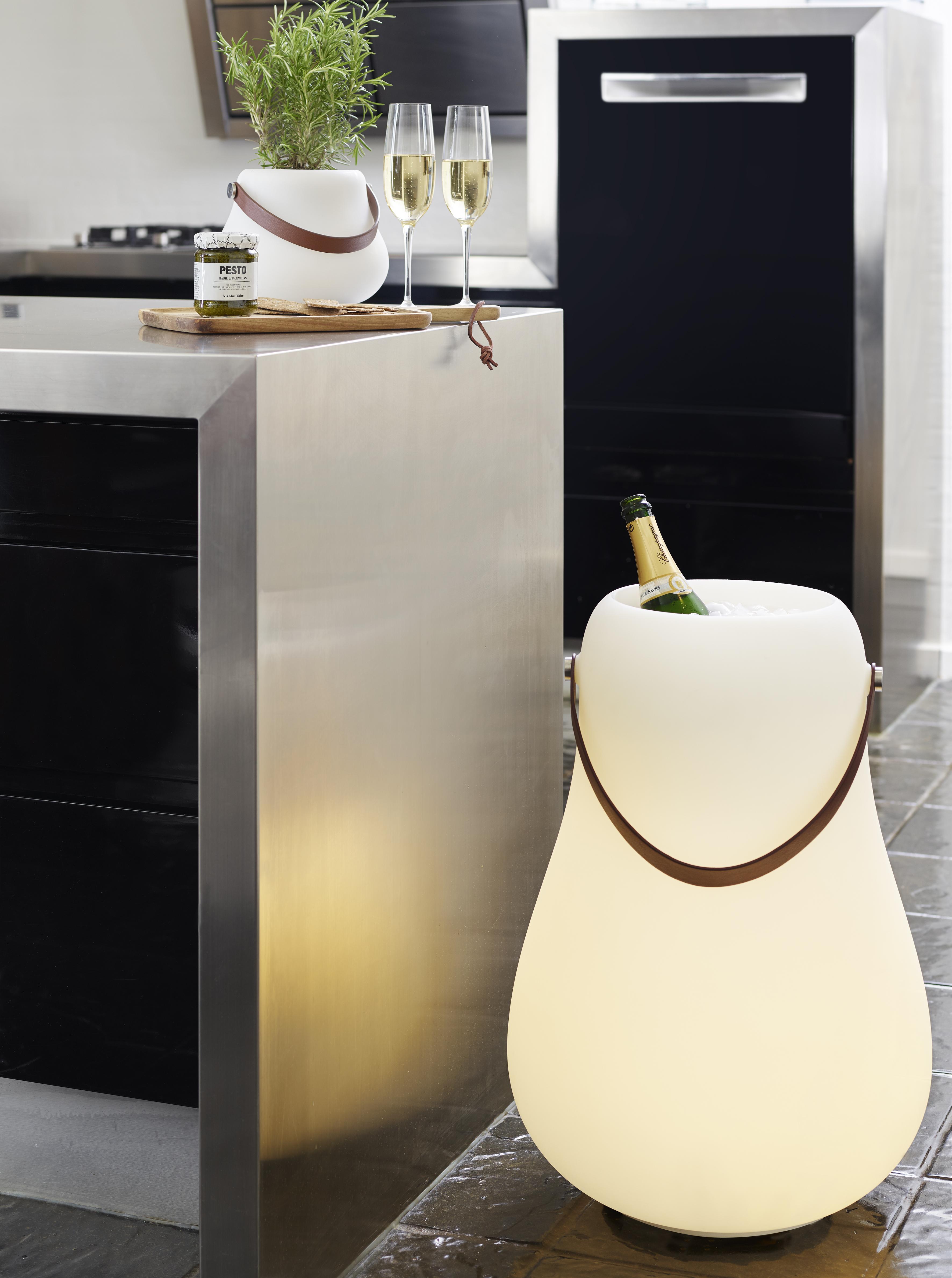 Ein kleiner leuchtender Blumentopf steht auf der Küche neben Sekt und Pesto
