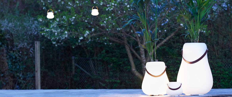 Drei Leuchtende Blumentöpfe im Dunkeln neben einem Baum