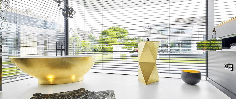 Ein Bad mit einer goldenen Badewanne und einem goldenen Waschbecken