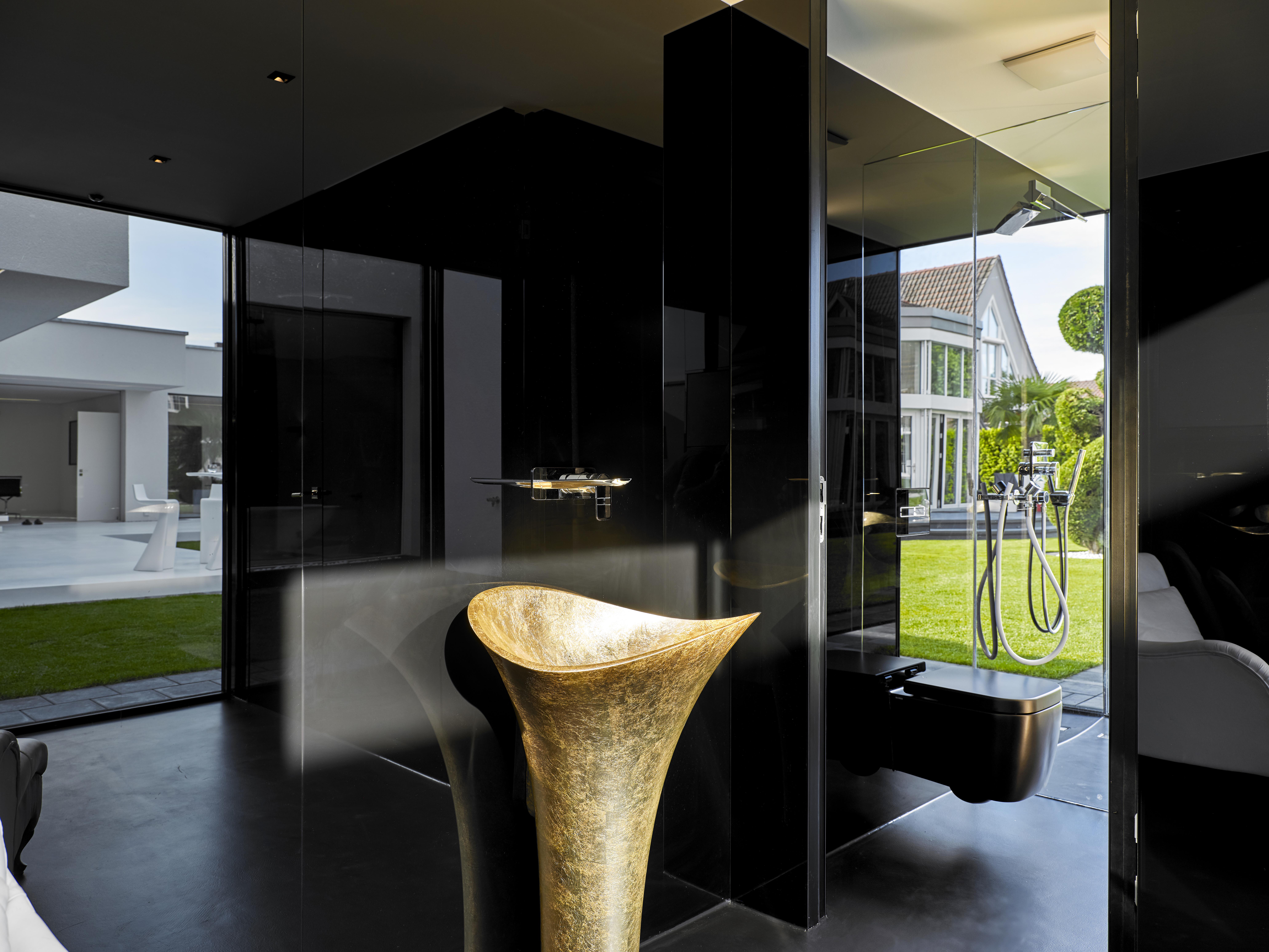 Ein schwarz gestaltetes Bad mit einem goldenen Waschbecken