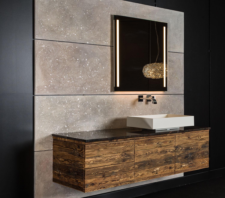 Ein Bad mit einem leuchtenden Spiegel und einem Unterbauschrank aus Holz
