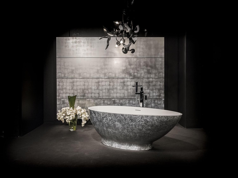 Ein schwarz gestaltetes Bad mit einer silbernen Badewanne