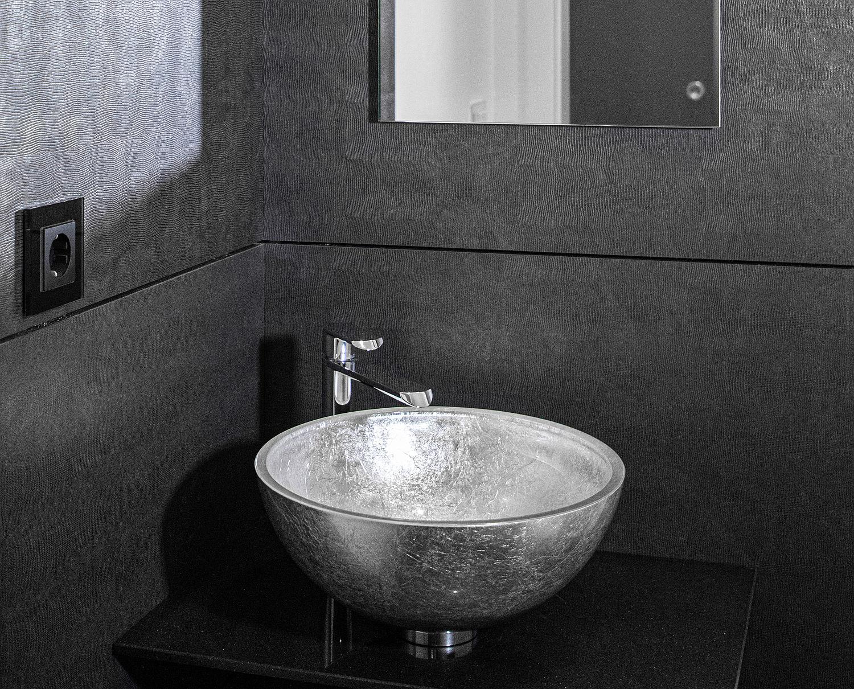 Ein dunkles gestaltetes Bad mit einem silbernen Waschbecken