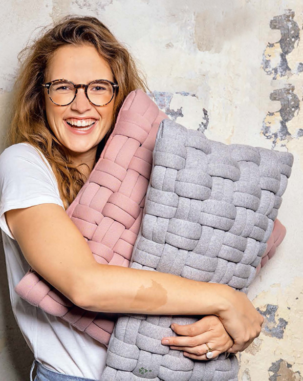 Eine Frau lacht und hebt zwei große Kissen im Arm