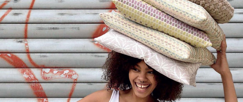 Eine Frau halt mehrere Kissen auf dem Kopf und lacht