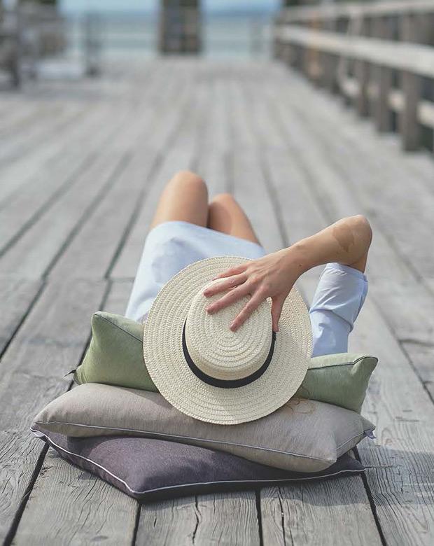 Eine Frau liegt auf mehreren Kissen auf einem Steg und verdeckt ihr Gesicht
