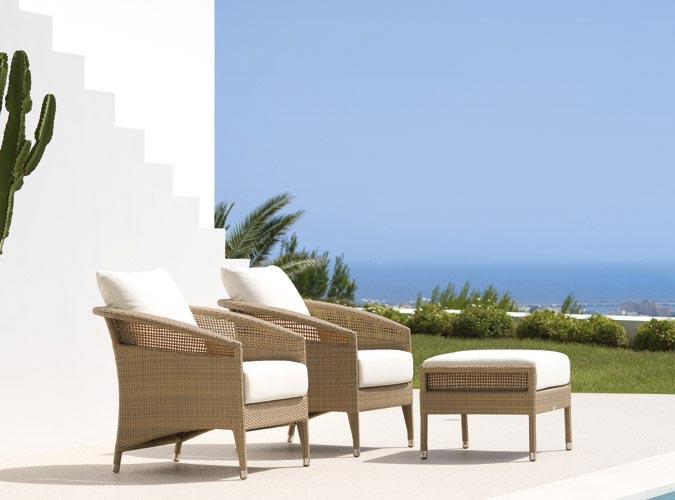 Zwei Outdoor Stühle stehen mit einem Hocker auf einer Sonnen-Terrasse