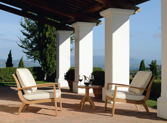 Zwei Outdoor Stühle stehen mit einem kleinen Tisch auf einer Sonnen-Terrasse