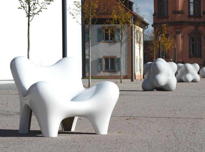 Ein stylischer Stuhl steht als Kunstobjekt in einer Innenstadt