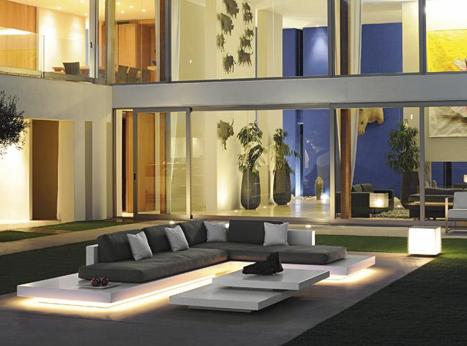 Eine Terrasse im Dunkeln mit einer leuchtenden Outdoor-Lounge