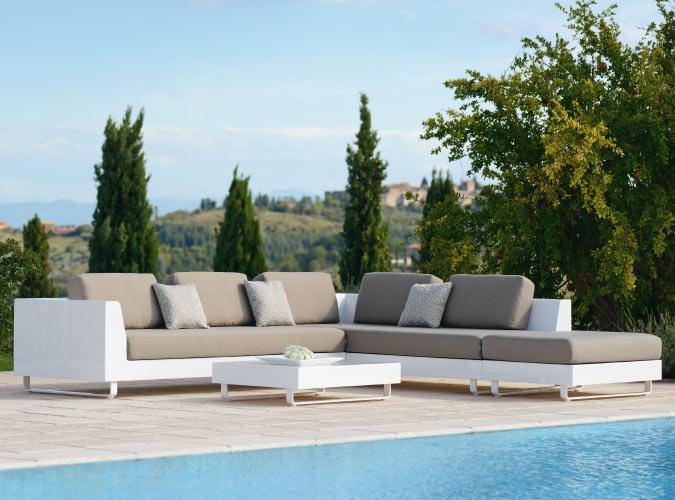 Eine Outdoor-Lounge steht neben einem Pool mit einer Landschaft im Hintergrund