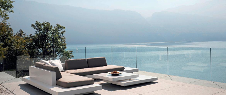Eine Outdoor-Lounge steht neben einem Pool mit Blick aufs Meer