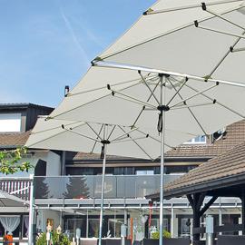 Graue Sonnenschirme auf einer Terrasse einer Gastronomie