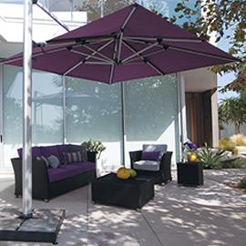 Ein Lila Sonnenschirm auf einer Terrasse neben einer Sitzecke