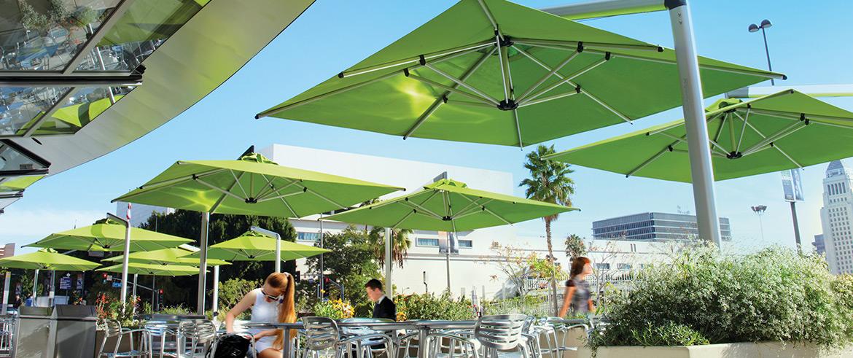 Grüne Sonnenschirme auf einer Terrasse einer Gastronomie