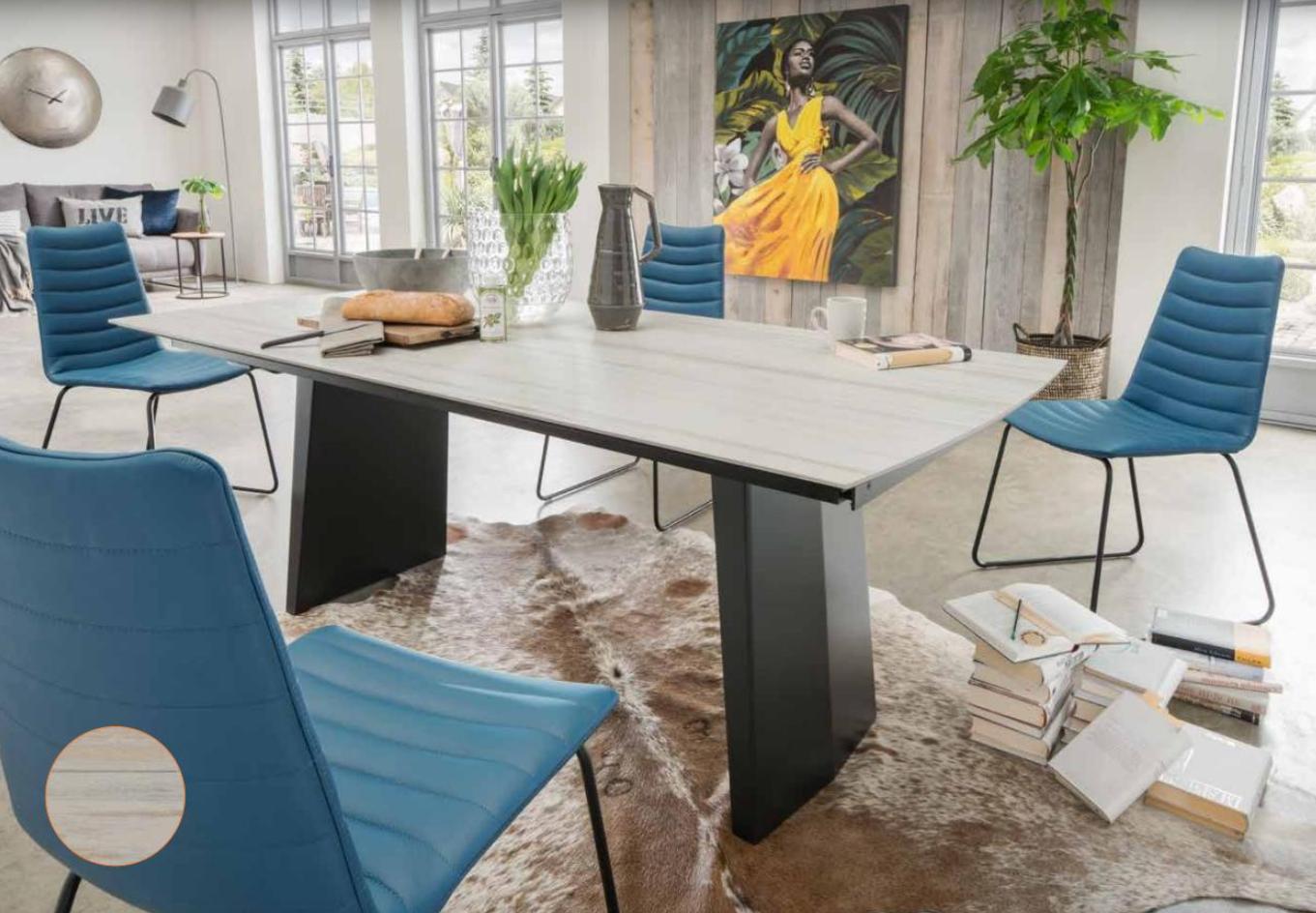 Ein Esszimmer mit blauen Stühlen und vielen Büchern auf dem Boden