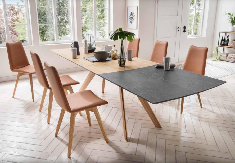 Ein Esszimmer mit orangenen Stühlen und einem zwei farbigen Tisch