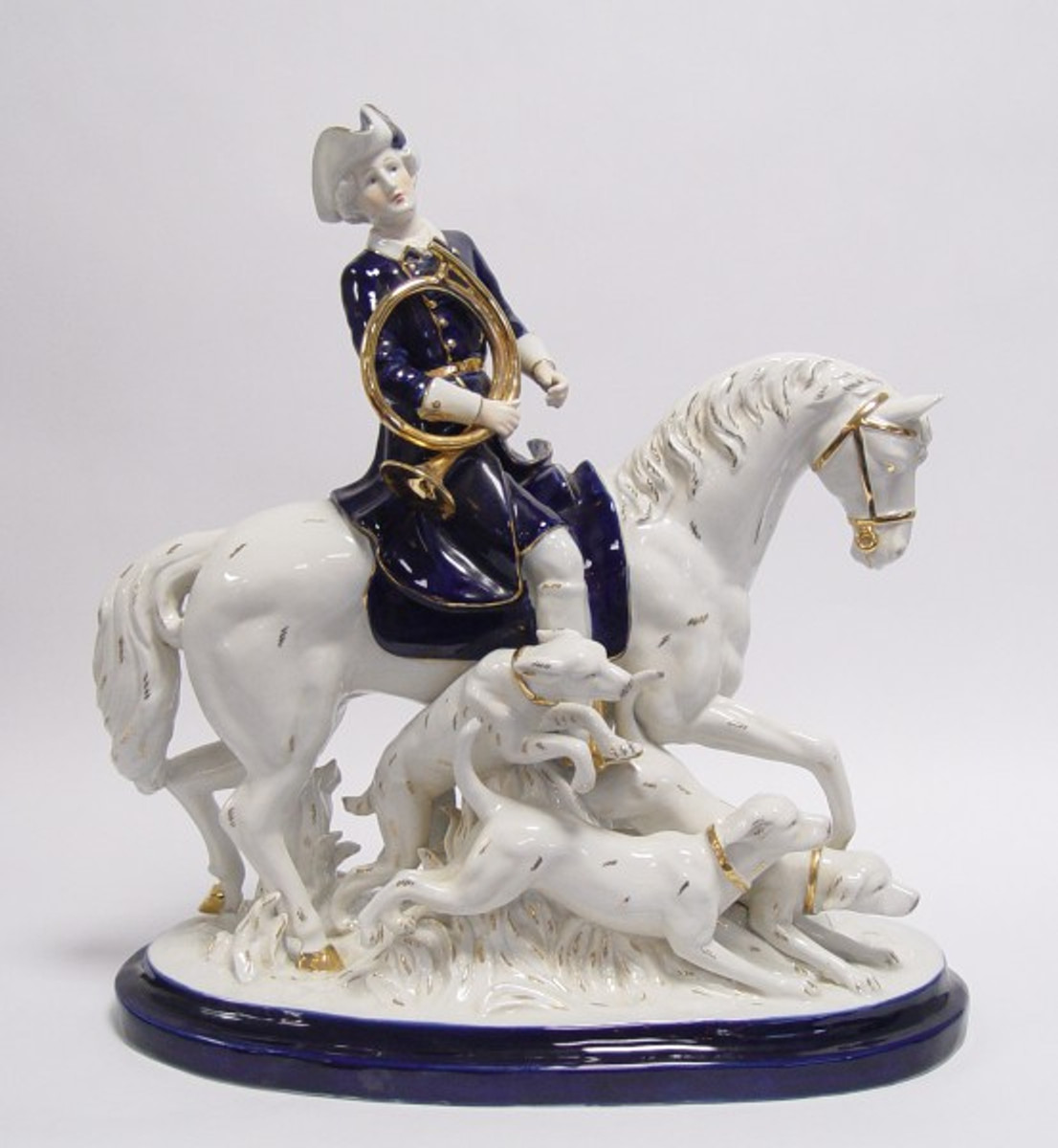 Reiter Porzellanfigur mit Horn und Trompete auf der Jagd als antike Dekoration.